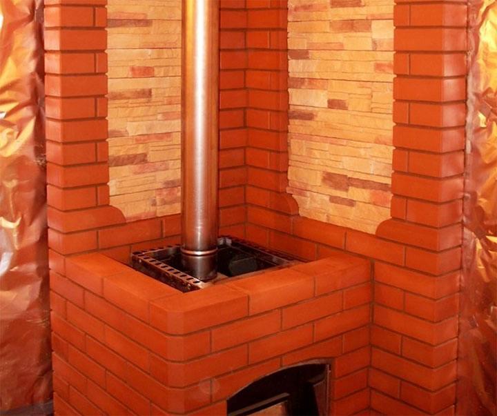 Металлическая банная печь обложенная красным кирпичом